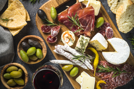 Antipasto board with sliced meat, ham, salami, cheese, olives an