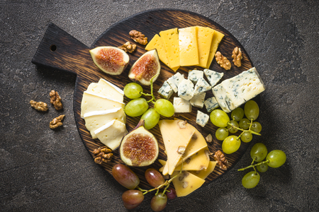 Cheese plate with grapes, figs and nuts on dark stone table. Delicatessen food. Top view. Stock Photo