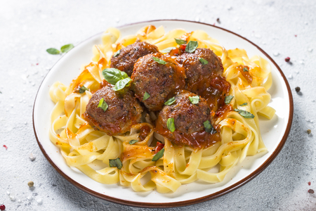 Meatballs in tomato sauce with pasta tagliatelle. Фото со стока