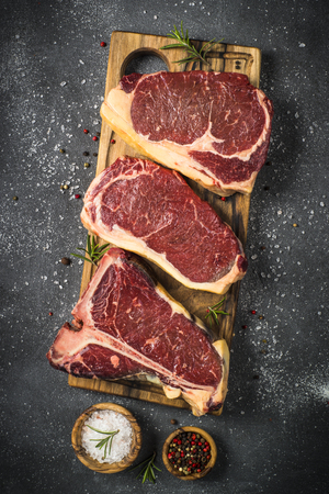 Raw meat beef steak. Black angus prime meat set - ribeye, striploin, t-bone steaks on cutting board. Top view on black table. Stock Photo