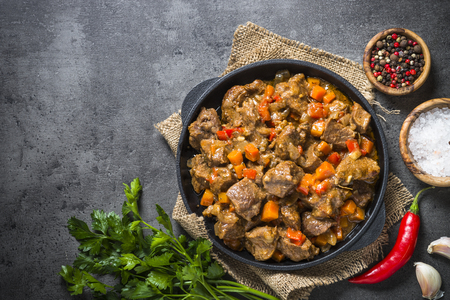 Beef stew with vegetables in iron pan on black.