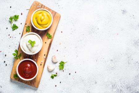 Zestaw sosów - majonez, musztarda, ketchup na białym.