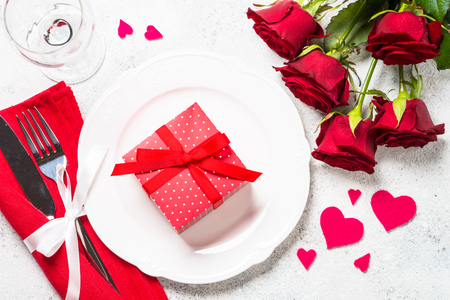 Valentines day table setting with plate, roses and present.
