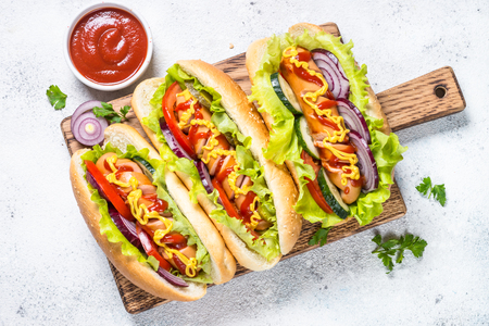 Hot dog with fresh vegetables on white top view. Standard-Bild