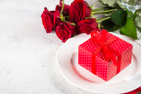 Holiday table setting with plate, roses and present. Stock Photo