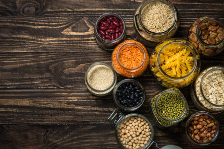 Cereals, Legumes, and beans in glass jars on  dark wooden table.
