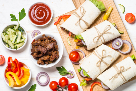 Burritos tortilla wraps with beef and vegetables on white. Stock Photo