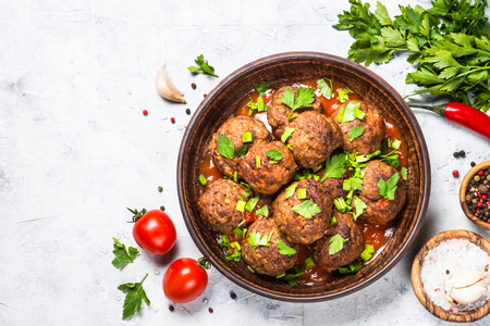 Meatballs in tomato sauce on light stone table top view.
