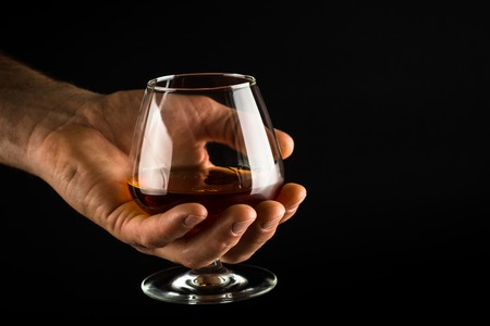 Man hold Cognac or brandy glass in his hand.
