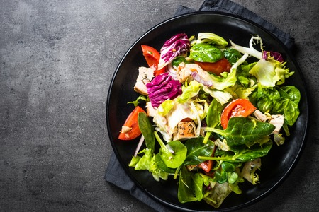 Green salad with chicken and vegetables on black. Stockfoto