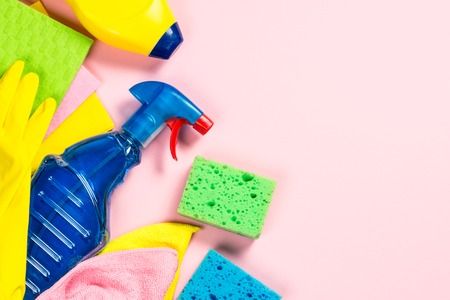 Cleaning product, household on pink flat lay.