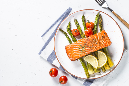 Grilled salmon fish fillet with asparagus and tomato on white craft plate. Top view on white stone table. Stock Photo