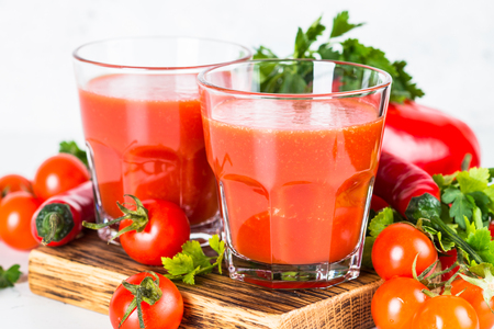 Tomato vegetable juice in glass on white. Stock Photo