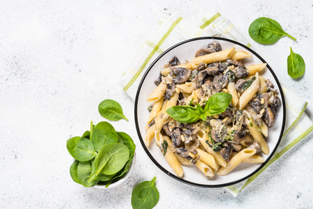 Pasta with mushrooms and spinach on white.