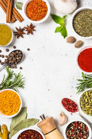 Spices and herbs on white stone table.