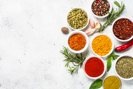 Set of spices and fresh herbs on white stone table. Curry, rosemary, turmeric, peppercorn, paprika, basil, cinnamon, cardamom and other. Top View with copy space. Фото со стока