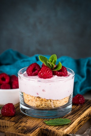 No baked cheesecake with raspberry in glass jar.