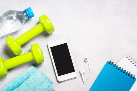Fitness background. Dumbbells, measuring tape, water and smartphone top view. Фото со стока