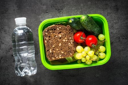Fiambrera con bocadillo, frutas y verduras.
