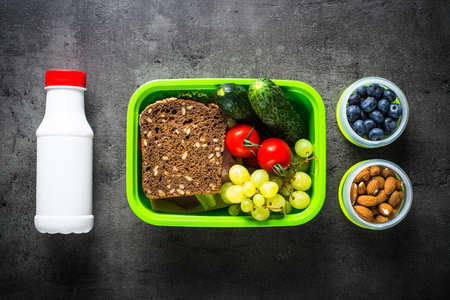 Lunch box with sandwich, vegetables, banana, yogurt, nuts and ber