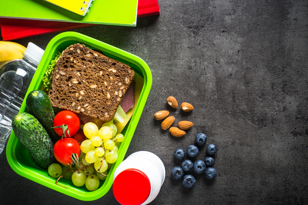 Lunch box with sandwich, fruit, vegetables, water.