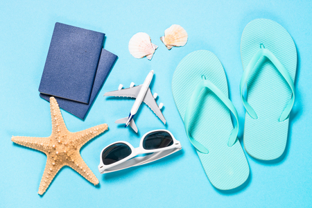 Summer flat lay background, travel concept. Blue flip flops, passports, sunglasses, airplane and starfish on blue background. Top view. Zdjęcie Seryjne - 122593902