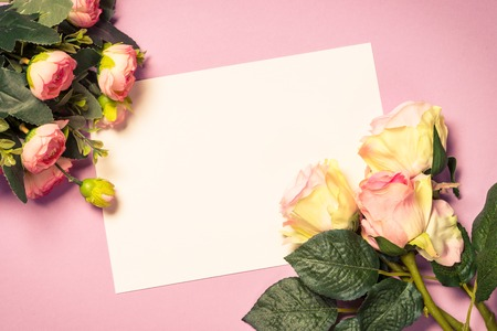 Empty paper sheet and rose flowers on pink background. Image toned, copy space.