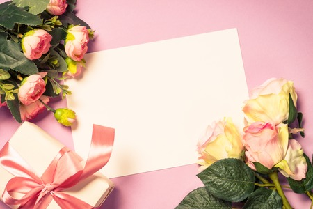 Empty paper sheet, flowers and present on pink background. Image toned, copy space.
