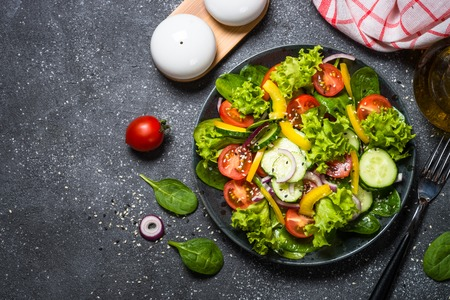 Ensalada de verduras frescas en negro.
