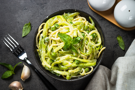 Pasta spaghetti with zucchini on black top view.