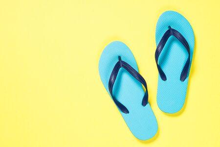 Blue flip flops on yelow. Reklamní fotografie