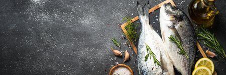 Raw dorado fish on black background.