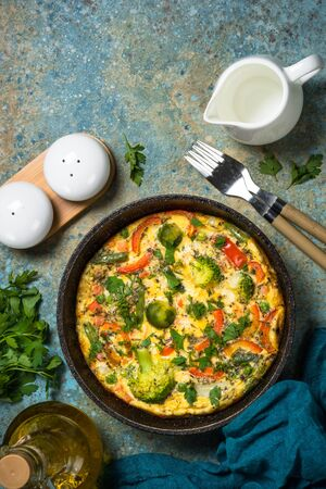 Frittata with fresh vegetables. Baked omelette with broccoli, paprika, brussels sprouts, green beans and herbs. Top view with copy space.