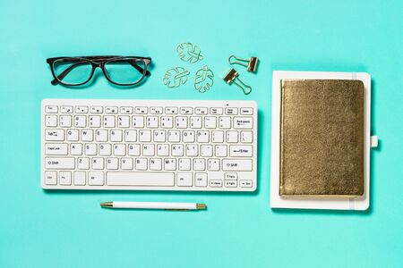 Office workplace with keyboard, notepad, glasses and pen