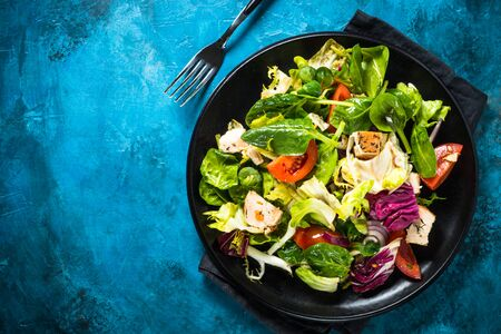 Green salad with chicken, salad leaves and vegetables. Healthy food, diet menu. Top view.