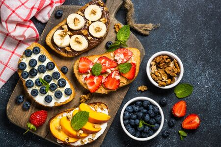 Sweet toast assortment. Chocolate banana, cream cheese and peach, peanut butter and strawberry, cream cheese and blueberry toasts. Black stone background, top view.