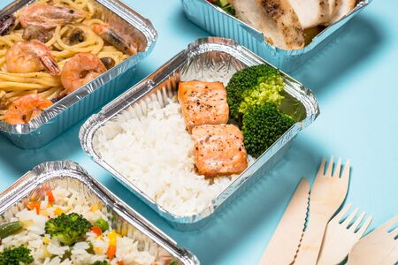 Food delivery. Different aluminium containers with healthy diet natural food on blue.