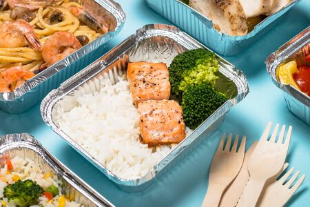 Food delivery. Different aluminium containers with healthy diet natural food on blue. 免版税图像 - 128327060