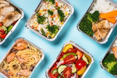 Food delivery. Different aluminium containers with healthy diet natural food. Top view on blue background.