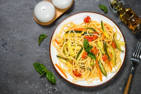 Vegetarian pasta. Pasta spaghetti with zucchini, carrot and tomatoes on grey stone background. Top view with copy space.