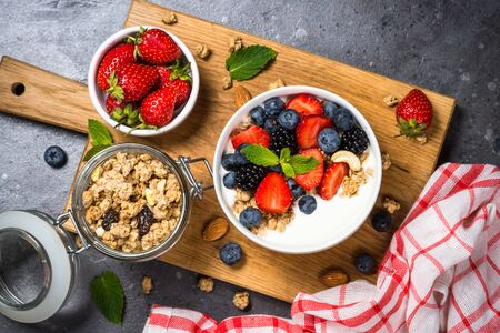 Greek yogurt granola with fresh berries on stone table, top view, copy space. Healthy food, snack or breakfast.