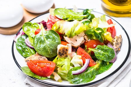 Green salad with chicken and vegetables on white.