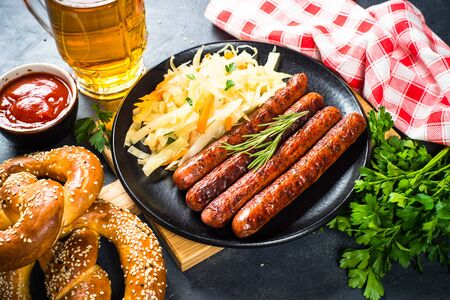 Oktoberfest food - sausage, sauerkraut, beer and bretzel.