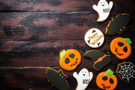 Halloween Gingerbread Cookies - pumpkin, ghosts, bat, on wooden table.