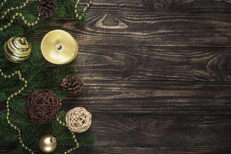 Christmas background with candle and decorations on dark wooden table. Imagens