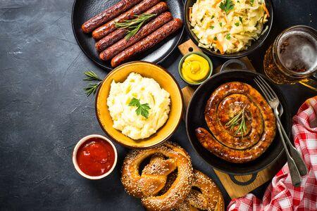 Oktoberfest food. Sauerkraut, sausage, pretzel, mashed potato and beer on black table. Top view.