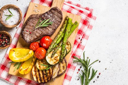 Grilled meat with vegetables on white stone table.