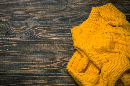 Yellow knitewear sweater on wooden table top view. Stok Fotoğraf