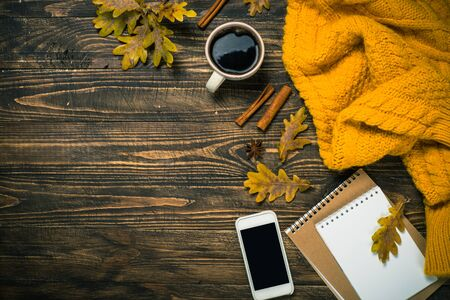 Autumn flat lay background with coffee, notebook, knitwear and yellow leaves. Creative workplace layout.
