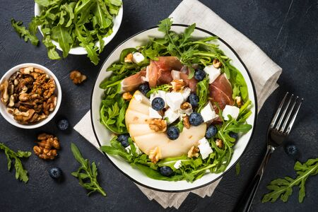 Green salad with leaves, fruit and jamon. Imagens